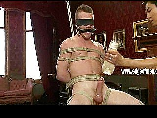 Tattooed Hunk Is Tied Up And Gagged While A Muscular Guy Jerks Him Off Forcefully